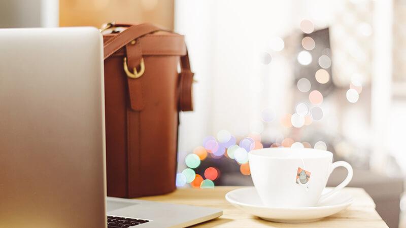 机の上にコーヒー、かばん、PCが置かれている様子