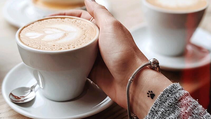 カフェで女性がカフェラテ系の飲み物を持とうとしている写真