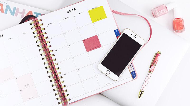 白い机の上に手帳とスマホ、ペンが置かれている写真