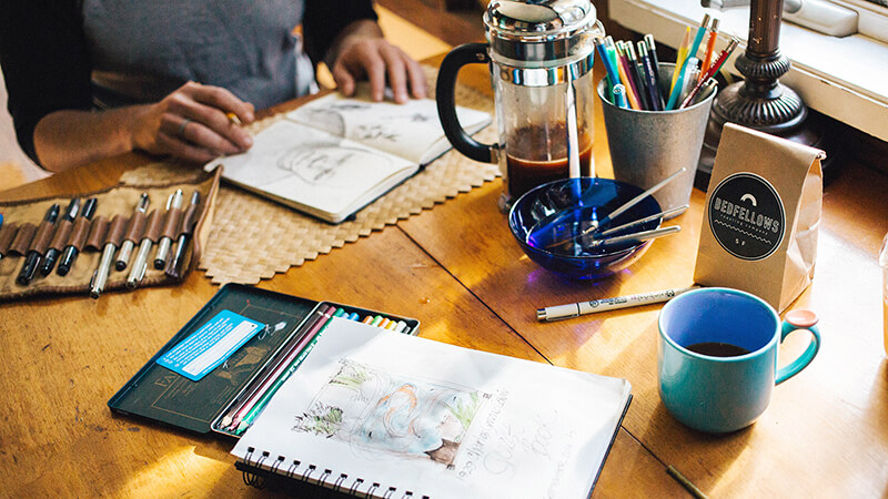 木の机の上にノートやペンが置かれている写真