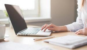 女性が茶色い机の上でPCを触っている画像