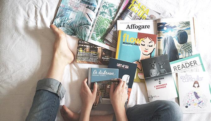 ベッドの上でたくさんの本を周りに置いて座っている女性の画像