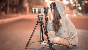 夜に道路の真ん中でフードを被った女性がカメラの前に座っている画像