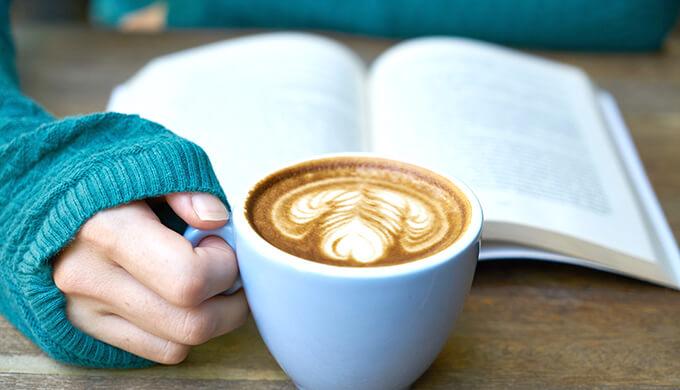 本を読みながらカフェラテを飲んでいる女性の手の画像