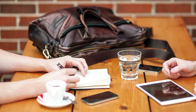 女性と男性が向き合って机の上に手を置いて、女性はノートを開いてぺんを持っている画像