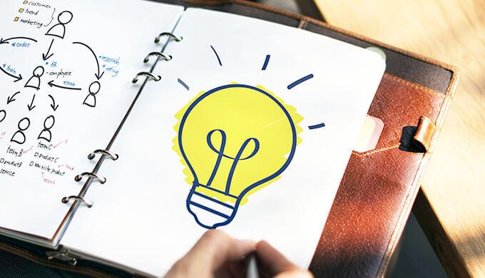 ノートに大きなライトの絵が書いてあるイイアイデアが浮かんだような画像