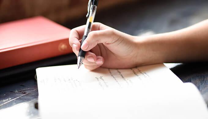 ノートを開いてペンを持って何か書こうとしている女性の手の画像