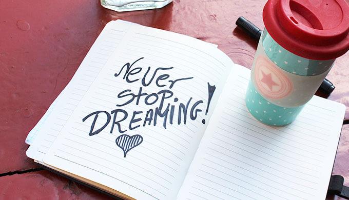 「NEVER STOP DREAMING!」と書かれたノートの上にコーヒーらしきものが乗っている画像
