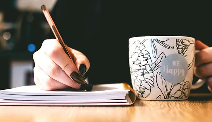 茶色い机の上でノートに何かを書き込んでいる女性の手元の画像