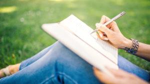 公園でノートを広げてペンで何か書いている女性の写真