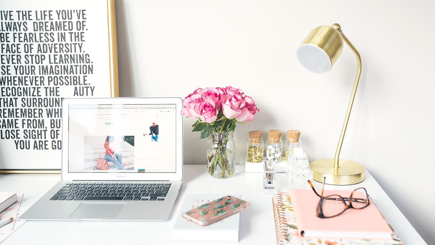 机の上にPCやお花、ノートなど可愛いものが並んでいる画像