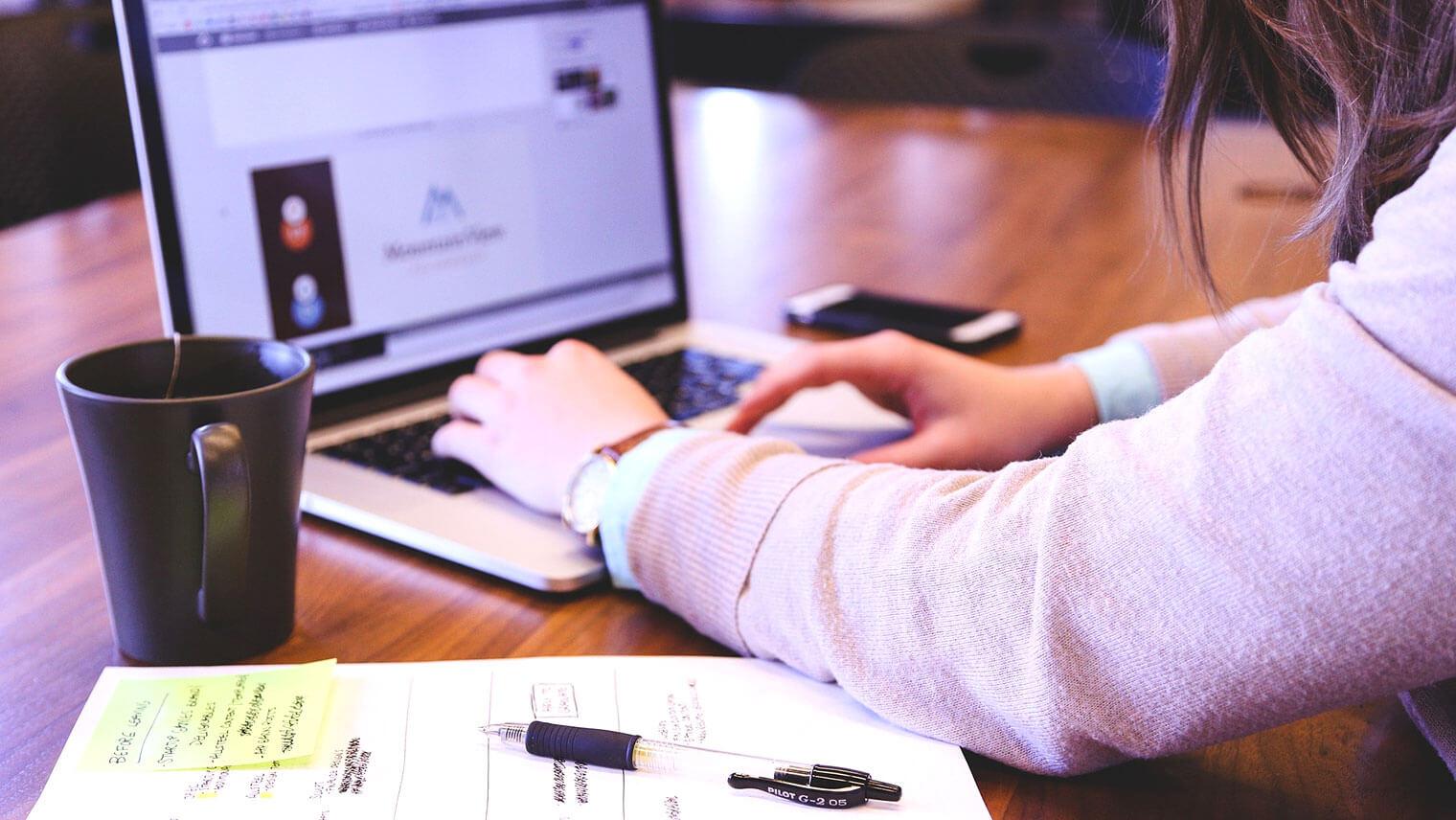 女性が机の上で資料を広げてPCをうっている画像