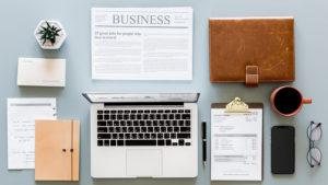 青グレーの机の上に、PCや手帳、新聞やスマホが置かれているのを上から撮った画像