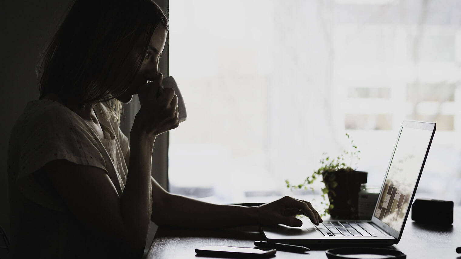 逆光の中でPCを触っている女性がコーヒーを飲んでいる暗めの画像