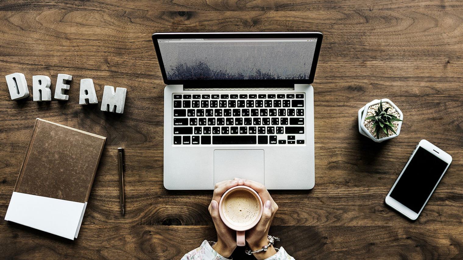 木の机の上に置かれたPCの前で、カフェラテを両手で抱えた女性の画像