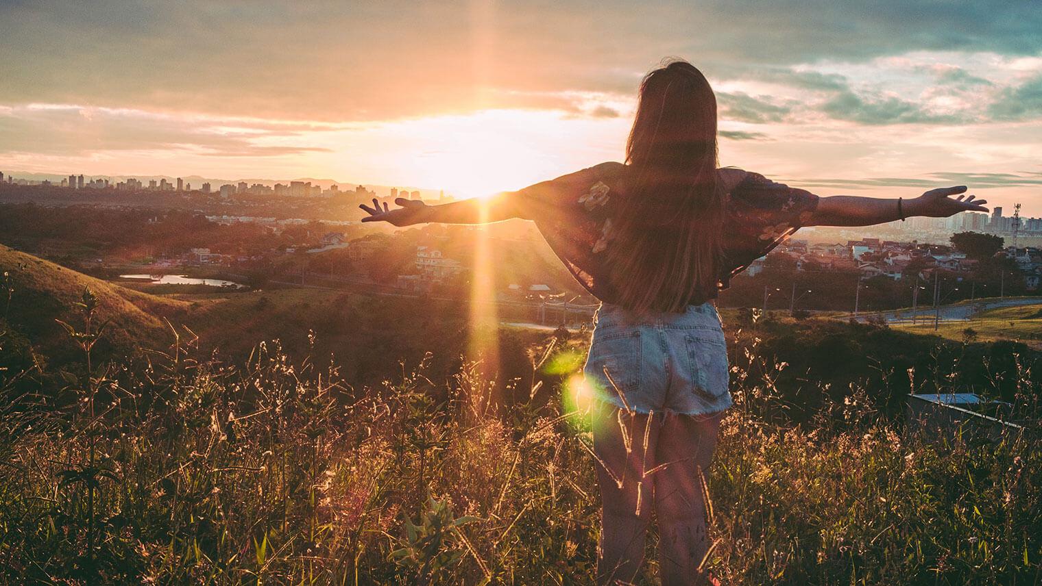 草原の中で短パンを履いた髪の長い女性が朝日に当たって両手を広げている写真