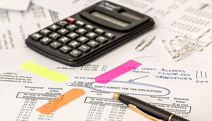 数字が並んだ書類の上にポストイットと電卓、ペンが置いてある画像
