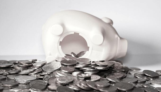 白い豚の貯金箱からお金(コイン)が溢れている画像