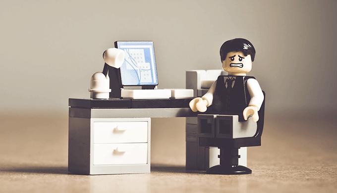 レゴブロックでスーツを着た男の人が机の前で困っている画像