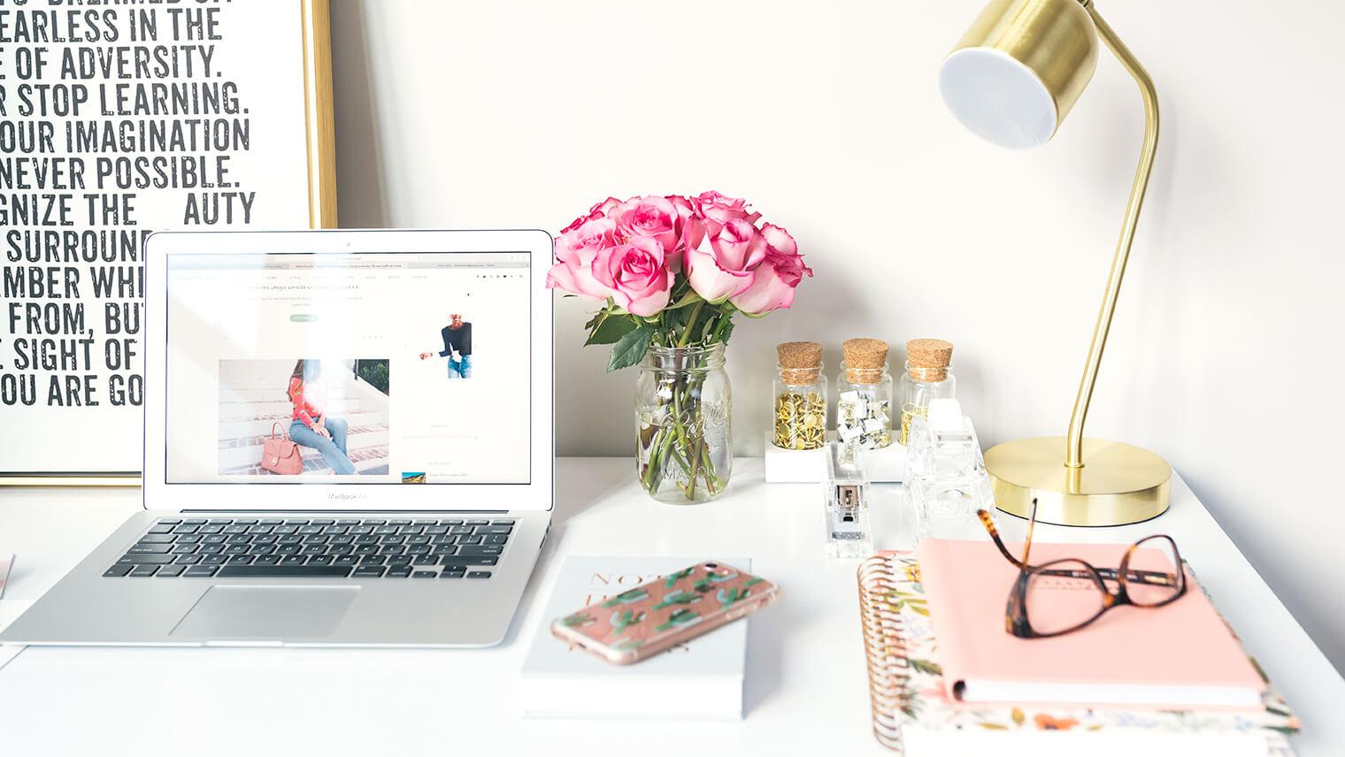 白い机の上に、macやお花、ノートやメガネが置かれている画像
