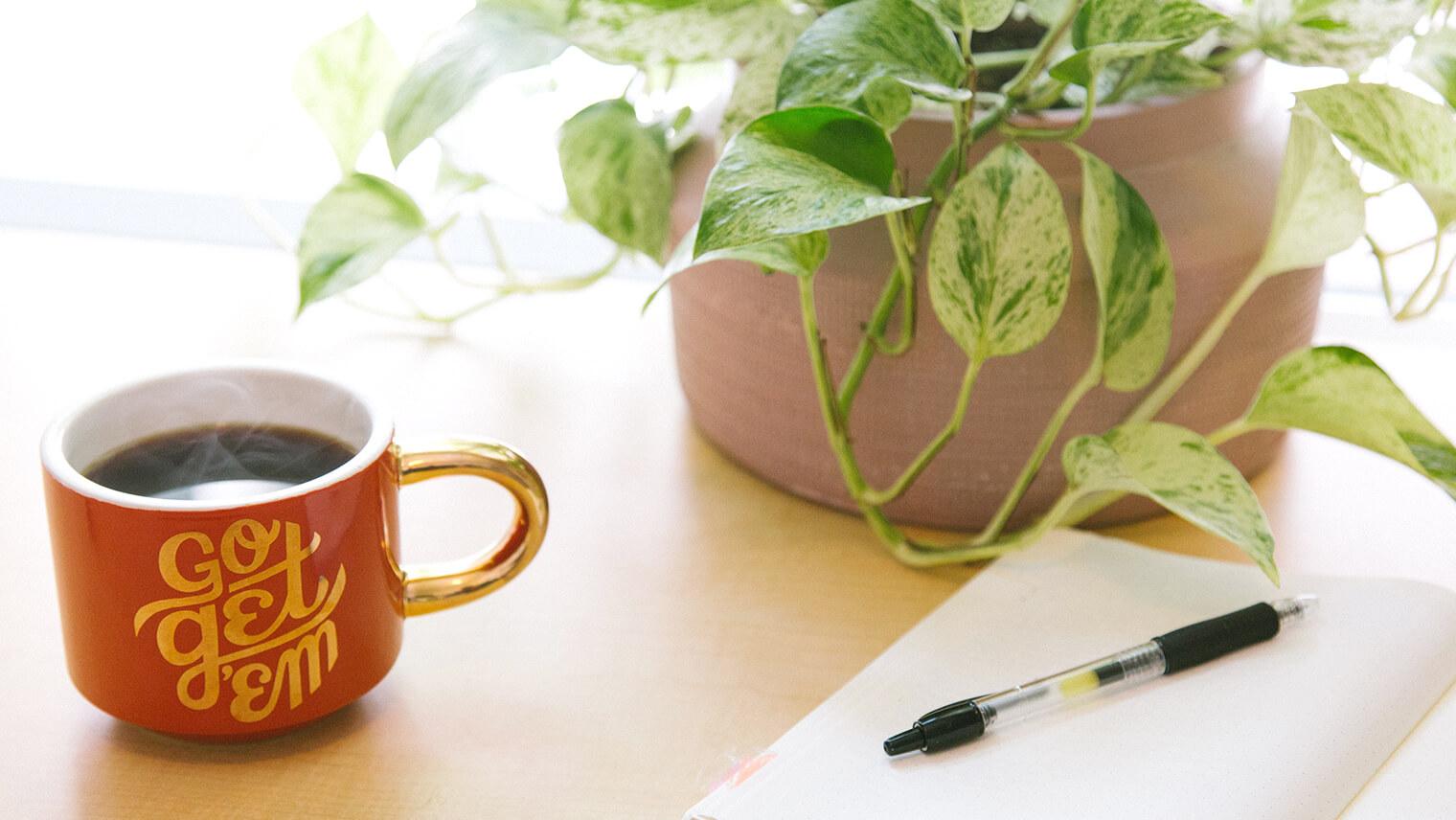 木の机の上に、赤いコップにコーヒーが入っていて、その隣にノートが広げられてペンが置かれている画像