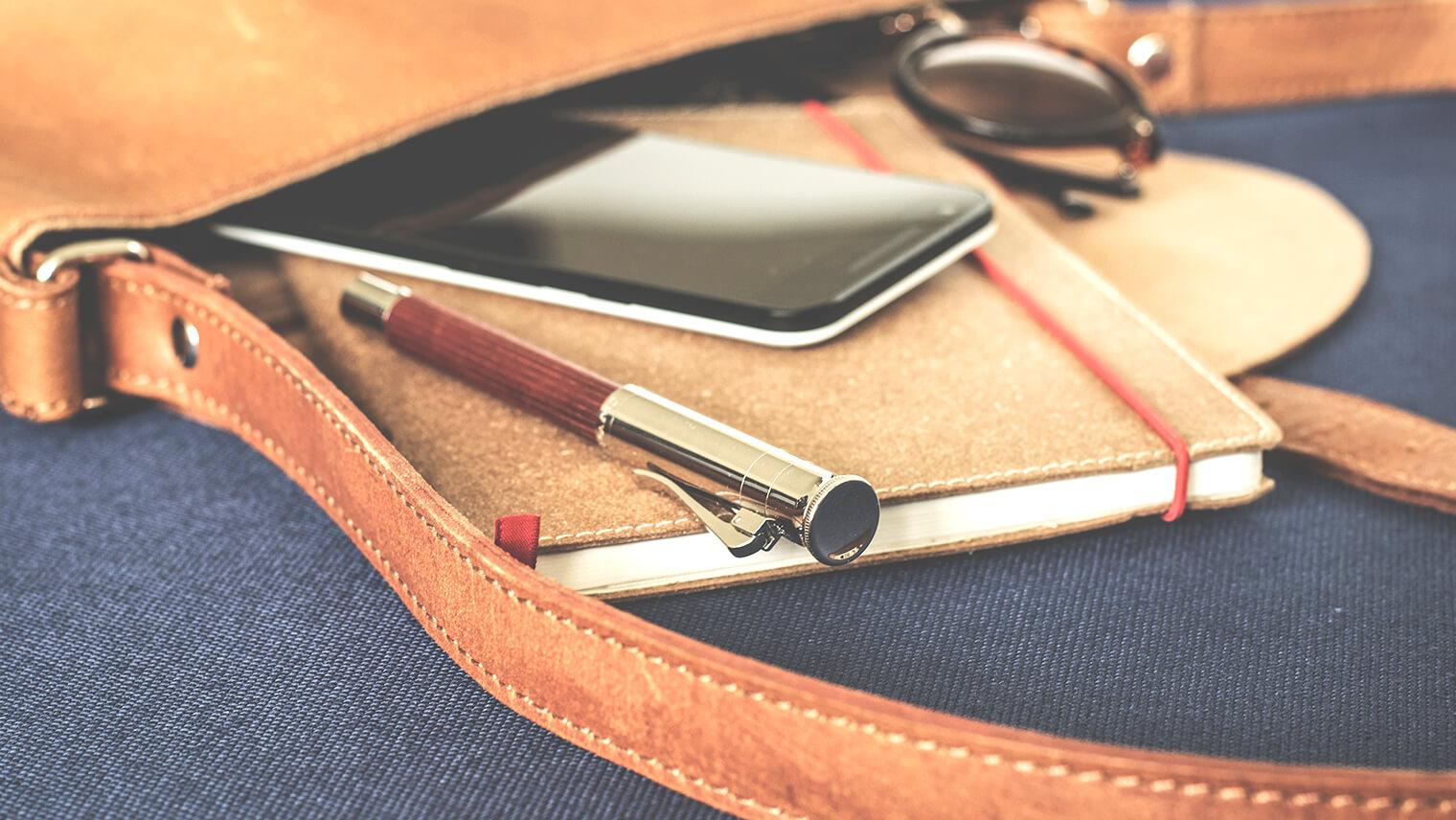 革の鞄の中からペンやiPhone、ノートが飛び出ている画像