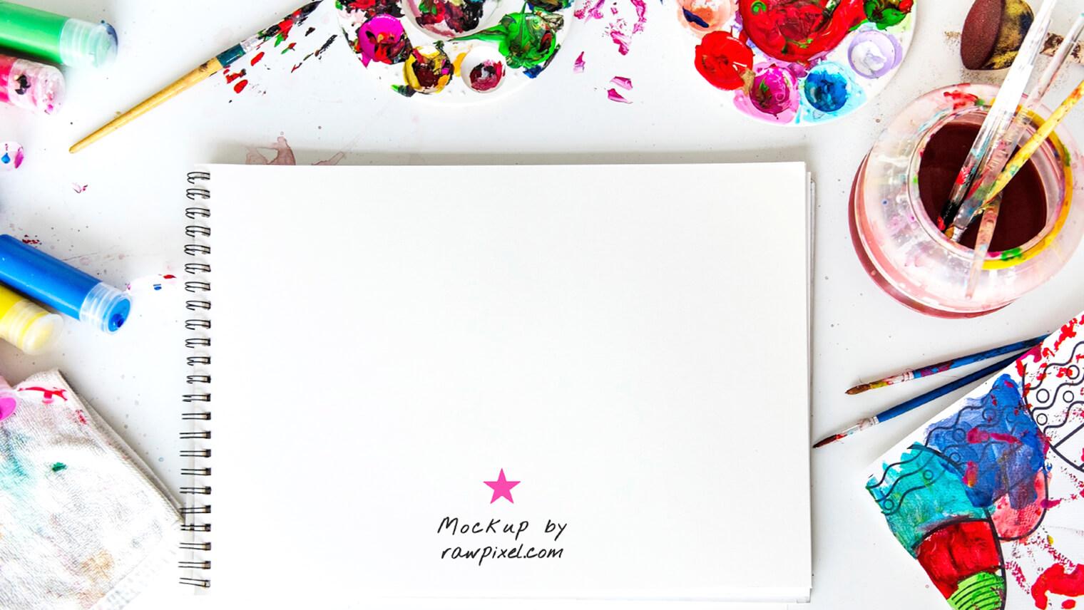 真ん中にノートを広げて周りには色鮮やかなペンや絵の具が転がっている画像