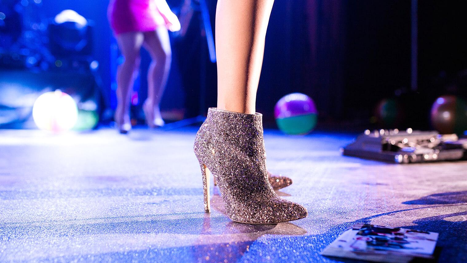舞台の上でシルバーのブーツを履いた女性の足