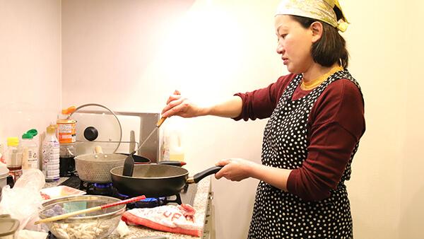 キッチンに立って女性が料理をしている写真