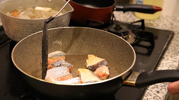 フライパンの中で鮭が炒められている写真